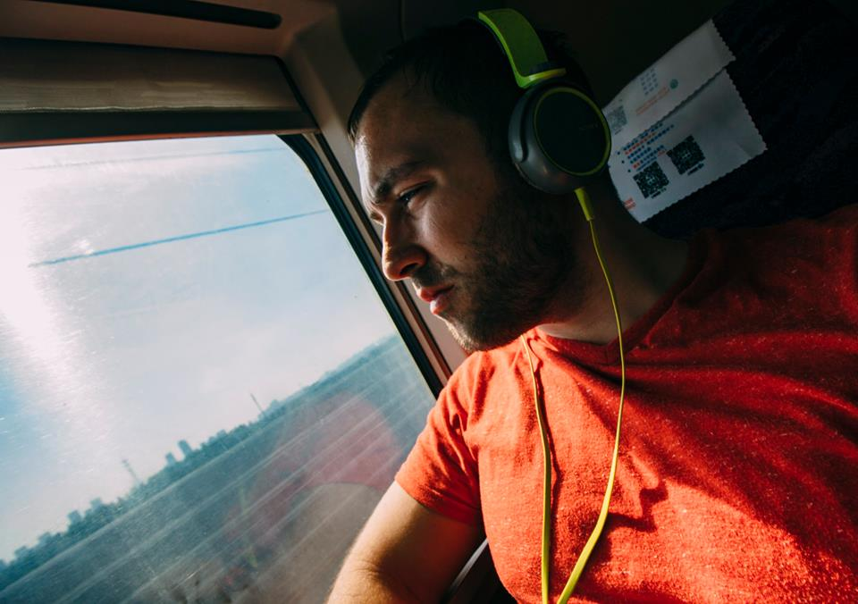 collin riding on a train with headphones