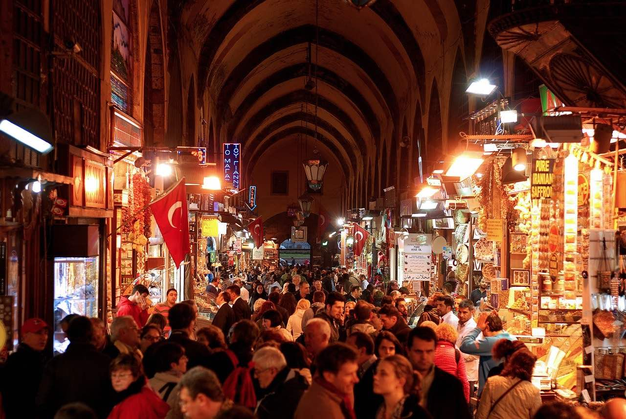 Crowds of people walking and shopping inside at night at the Grand Market Istanbul Turkey