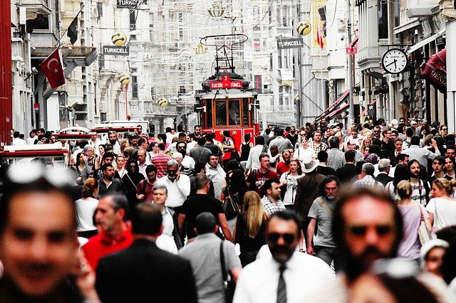 view of crowded istikal caddesi pedestrian shopping street in istanbul turkey with red tram in middle