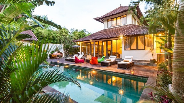 a stunning villa with pool in bali with palms and lounge chairs