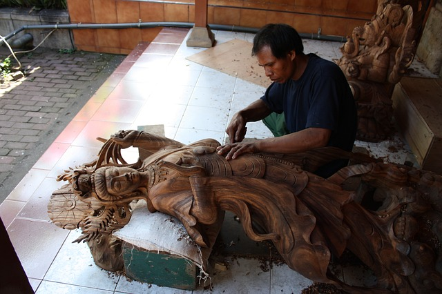 skilled craftsman carves large wooden statue in bali indonesia