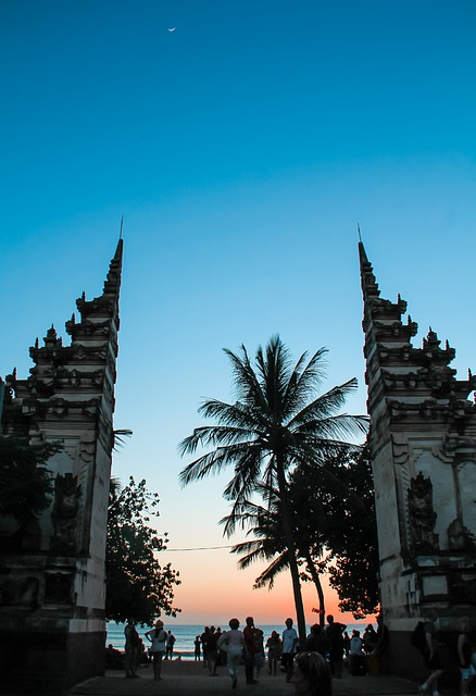candi bentar structure marking entrance to kuta beach in bali at sunset with people and palm trees