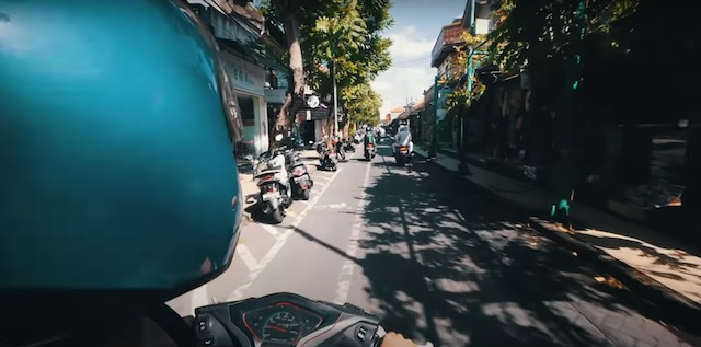 riding a motorbike taxi in kuta bali down narrow streets with markets