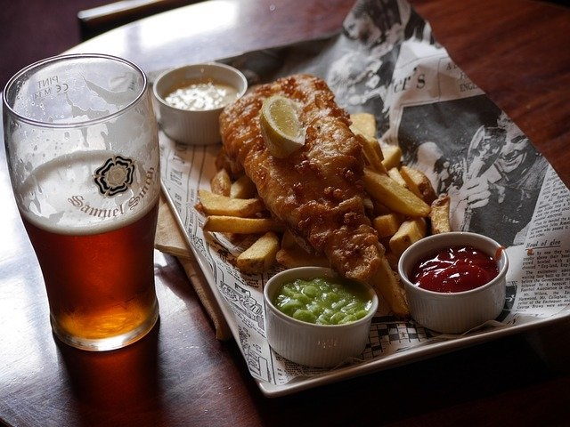 Inside a British Pub with beer and fish and chips meal - a traditional food in England you must try!