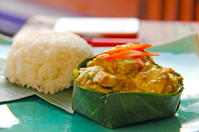 Up close photo of fish amok in a leaf bowl with rice a traditional cambodian dish