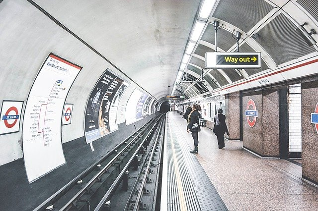 standing inside a london Tube underground station waiting for the train with bright lights and signs
