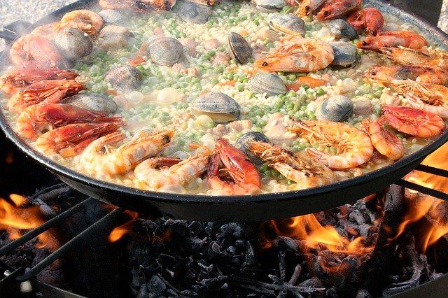 Big pan of seafood paella cooking over hot fire in spain