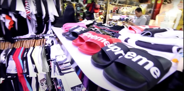 up close picture of supreme sandles and t-shirts on rack in luohu commercial market shenzhen china