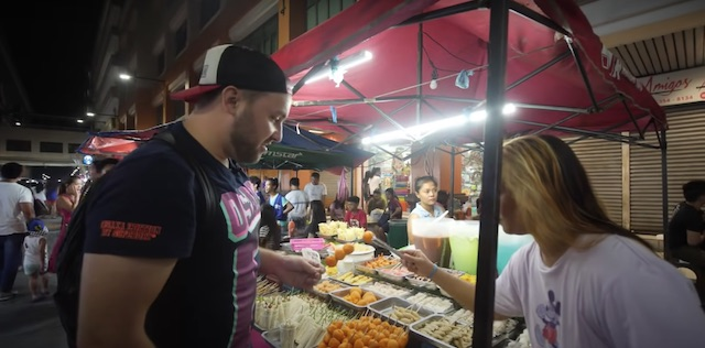 collin eating street food on a stick in the Divisoria market manila philippines