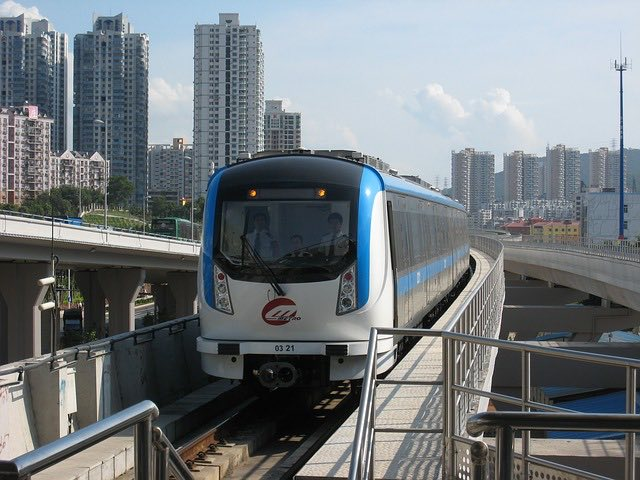 metro train in shenzhen on track with buildings around
