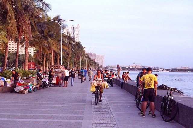 evening along manila bay in the philippines with locals hanging out and fishing