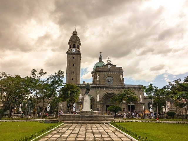 cathedral in manila philippines with green grass and cloudy sky makes for cool light at dusk