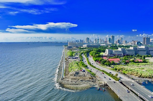 aerial shot of coast line and city of manila philippines with buildings and greenery
